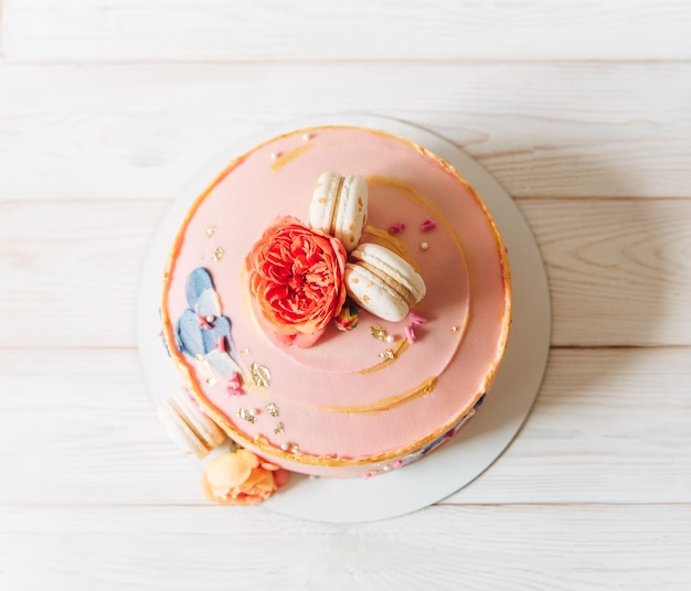 Eleganter kuchen. hellrosa mit blumen und makrone. weißer hintergrund. draufsicht