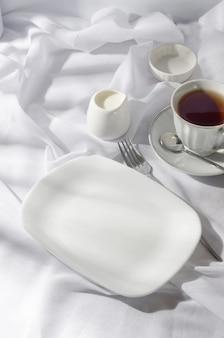 Eleganter leerer teller, besteck, tasse kaffee am sonnigen morgen, sauberer weißer tischdeckenhintergrund, draufsicht. frühstückstisch gedeck in weißer farbe.