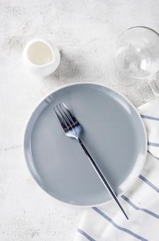 Eleganter leerer teller, besteck, tasse kaffee zum morgenessen, heller tischhintergrund, draufsicht. frühstückstisch gedeck in weißer farbe.