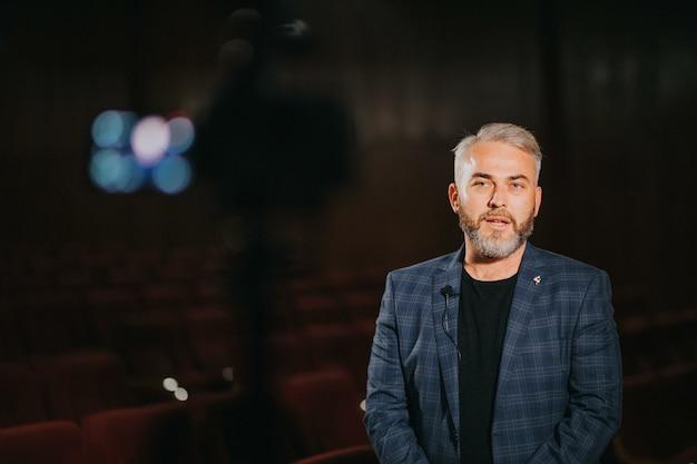 Eleganter männlicher theater- und filmregisseur, der im auditorium ein interview gibt