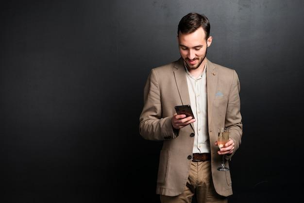 Eleganter mann an der party, die telefon betrachtet