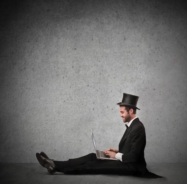 Eleganter mann, der an einem laptop arbeitet