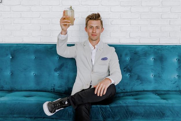 Eleganter mann, der auf blauem sofa sitzt