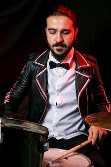 Eleganter mann, der auf trommelsatz spielt