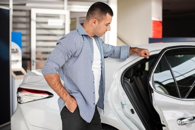 Eleganter mann, der ein auto an der verkaufsstelle überprüft