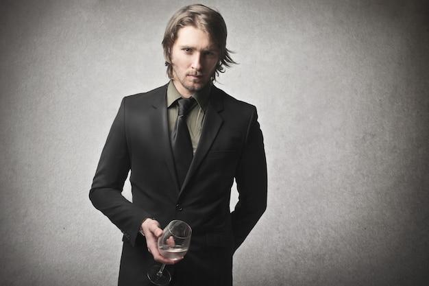 Eleganter mann, der ein glas hält