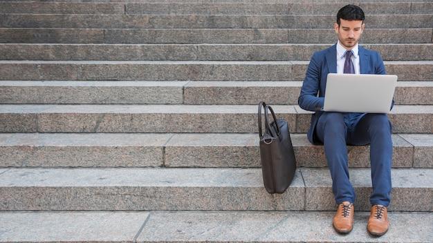 Eleganter mann, der laptop auf schritten verwendet