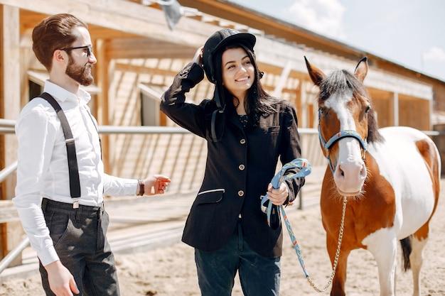 Eleganter mann, der nahe bei pferd in einer ranch mit mädchen steht