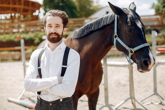Eleganter mann, der nahe bei pferd in einer ranch steht
