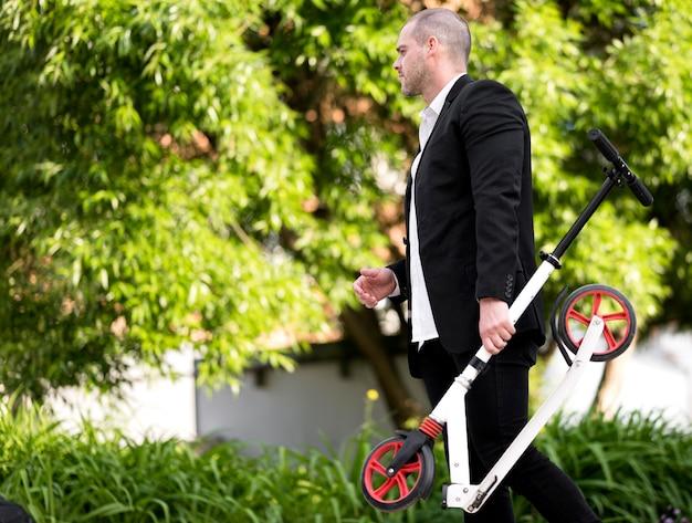 Eleganter mann, der roller im freien trägt