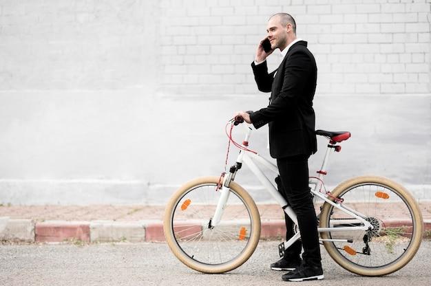 Eleganter mann der seitenansicht mit fahrrad im freien
