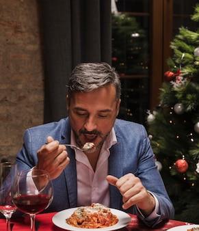 Eleganter mann, der weihnachtsessen genießt