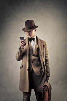 Eleganter mann der weinleseart mit einem smartphone