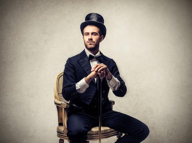 Eleganter mann, der zylinder trägt und auf einem stuhl sitzt