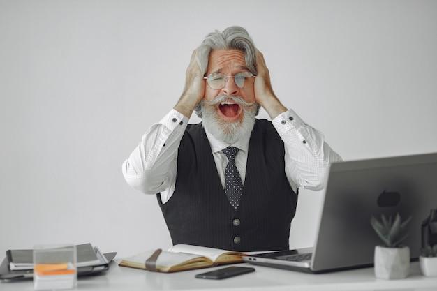 Eleganter mann im amt. geschäftsmann im weißen hemd. mann arbeitet mit laptop.
