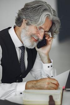 Eleganter mann im amt. geschäftsmann im weißen hemd. mann arbeitet mit telefon.