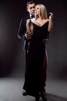 Eleganter mann im anzug umarmt sanft eine sexy frau im abendkleid, porträt auf schwarzer oberfläche