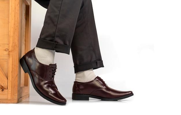Eleganter mann im geschäftskleid, welches die braunen schuhe sitzen auf hölzernem kasten und sein bein stillstehen trägt