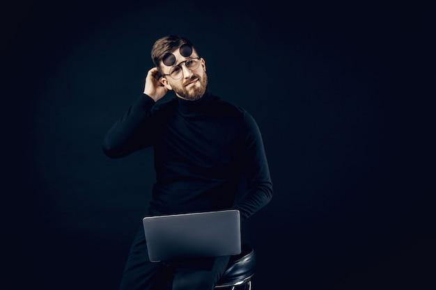 Eleganter mann in der schwarzen kleidung und in den klappgläsern, die auf der idee sitzt mit laptop gedanklich lösen.