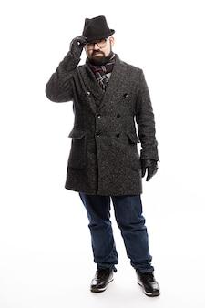 Eleganter mann mit bart in mantel und hut. er steht in vollem wachstum auf einer weißen wand und hält sich an seinem hut fest. vertikale.