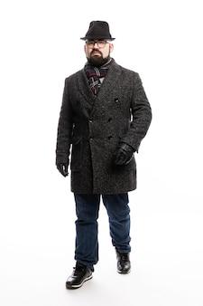 Eleganter mann mit bart in mantel und hut. in voller länge steht auf einer weißen wand. vertikale.