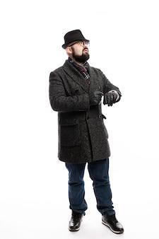 Eleganter mann mit bart in mantel und hut schaut auf seine uhr. vollständige höhe. weiße wand. vertikale.