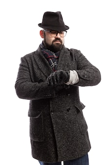 Eleganter mann mit bart in mantel und hut schaut auf seine uhr. weiße wand. vertikale.