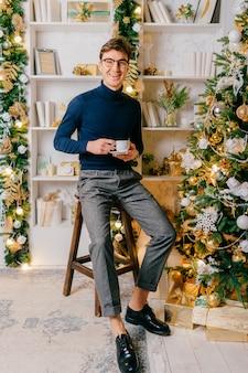 Eleganter mann mit dem positiven emotionalen gesicht, das für kamera mit tasse kaffee im gemütlichen raum mit cristmas baum aufwirft.