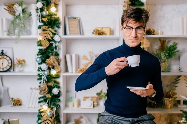 Eleganter mann mit dem positiven emotionalen gesicht, das für kamera mit tasse kaffee im gemütlichen raum mit cristmas baum- und neujahrsdekorationen aufwirft