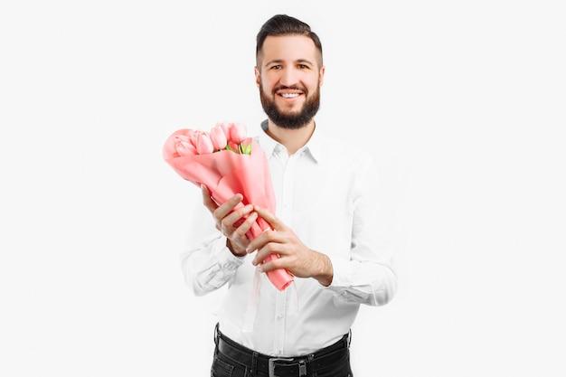 Eleganter mann mit einem bart, der einen strauß tulpen hält, ein geschenk für valentinstag