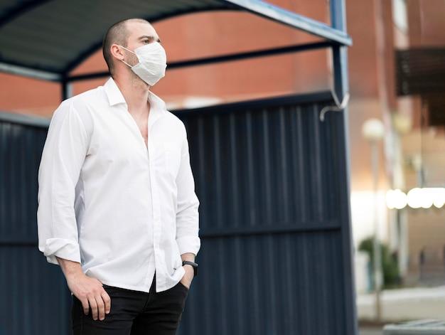 Eleganter mann mit gesichtsmaske, die auf den bus wartet