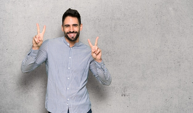 Eleganter mann mit hemd lächelnd und zeigt siegeszeichen mit beiden händen über strukturierte wand