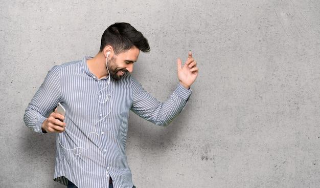 Eleganter mann mit hörender musik des hemdes mit dem telefon über strukturierter wand