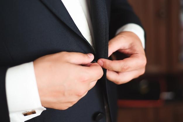 Eleganter mann putzt sich mit hochzeitsanzug
