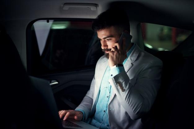 Eleganter moderner geschäftsmann mit laptop auf dem rücksitz, der auf einem handy spricht.