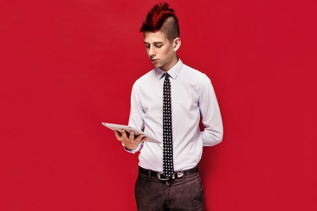 Eleganter punk mit tablette gegen roten hintergrund