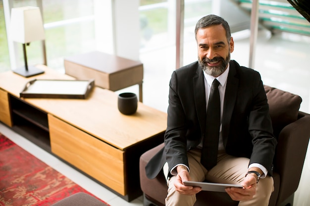 Eleganter reifer geschäftsmann, der multitasking multimedia digital tablet verwendet