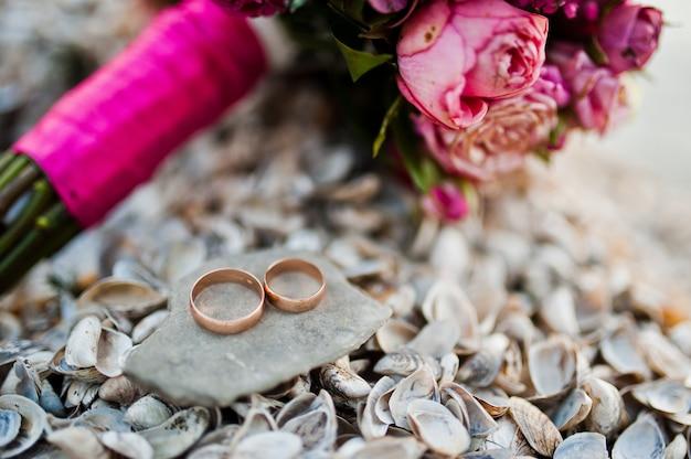 Eleganter rosa hochzeitsblumenstrauß mit ringen an den oberteilen