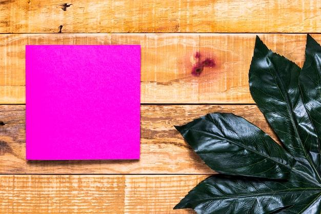 Eleganter rosa umschlag mit hölzernem hintergrund