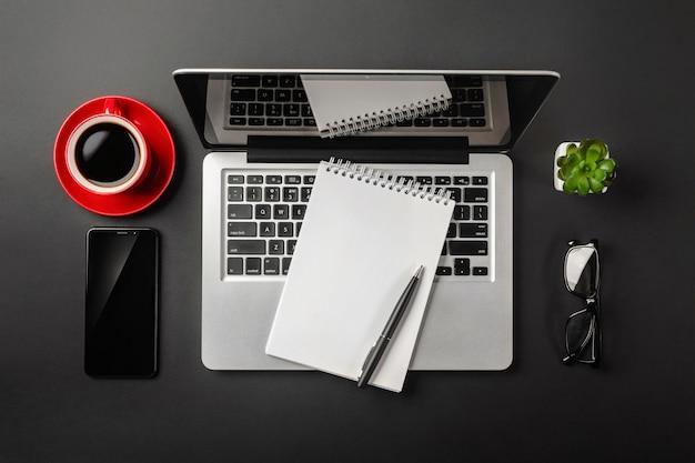 Eleganter schwarzer bürodesktop mit laptop, notizbuch, rotem tasse kaffee und handy. ansicht von oben.