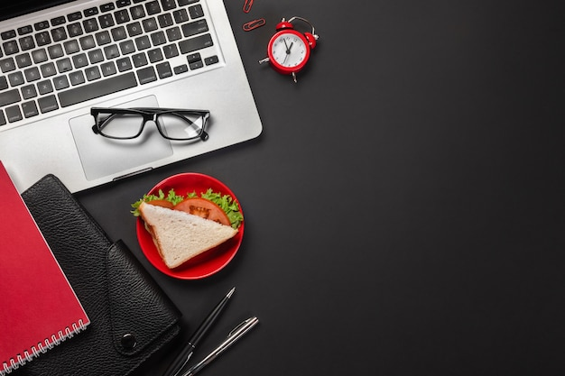 Eleganter schwarzer bürodesktop mit laptop, tasse kaffee und einem sandwich zum mittagessen. ansicht von oben