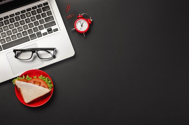 Eleganter schwarzer bürodesktop mit laptop, tasse kaffee und einem sandwich zum mittagessen. draufsicht mit kopienraum