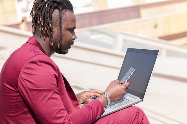 Eleganter schwarzer geschäftsmann arbeitet im freien mit laptop und telefon, technologie und remote-work-konzept