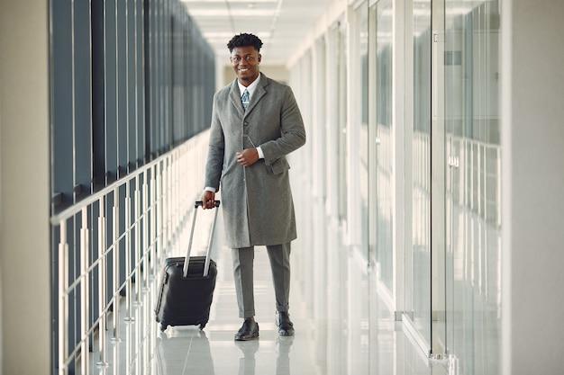 Eleganter schwarzer mann am flughafen mit einem koffer