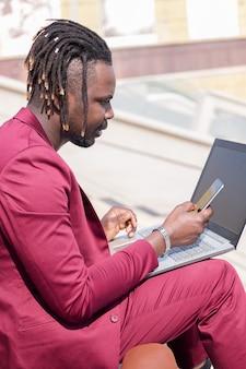 Eleganter schwarzer mann, der mit laptop und telefon arbeitet
