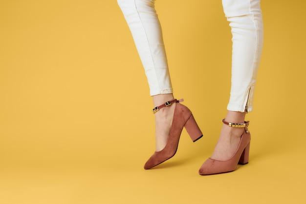 Eleganter stil des eleganten gelben hintergrunds der modischen schuhe der weiblichen füße modischer schuhe. hochwertiges foto