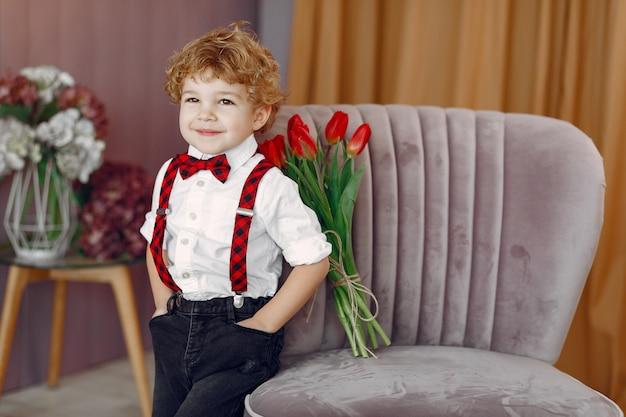 Eleganter süßer kleiner junge mit strauß tulpe