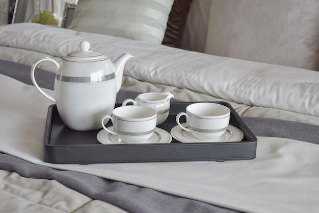 Eleganter teeschalensatz auf schwarzem behälter im modernen schlafzimmerinnenraum
