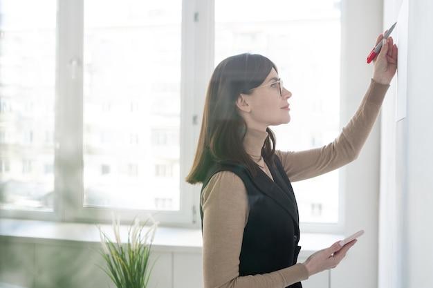 Eleganter trainer mit smartphone, der auf whiteboard aufschreibt, während präsentation für studenten macht