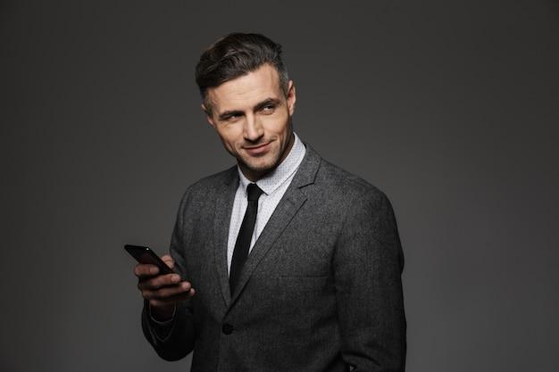 Eleganter trendiger mann, gekleidet in geschäftskostüm, das smartphone hält und mit lächeln beiseite schaut, lokalisiert über graue wand